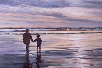 A boy and his father stride alongside each other along a beach at sunset in California.