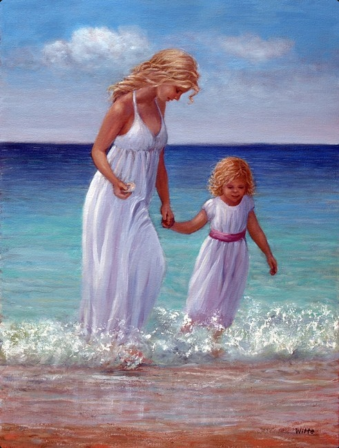 A mother and daughter, adorned in white lace, wade gently through shallow ocean surf.