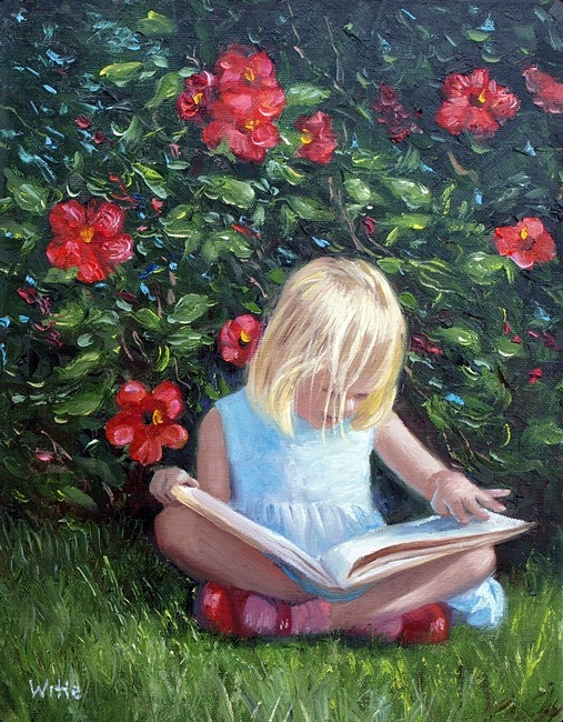 A young blond-haired girl reads a book outside in a garden, beside a hibiscus flower bush.