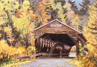 The entrance to an old covered bridge in Vermont, with peak foliage surrounding.