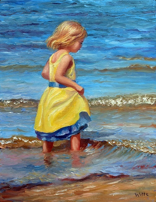 A young girl in a yellow skirt steps carefully into the ocean surf.