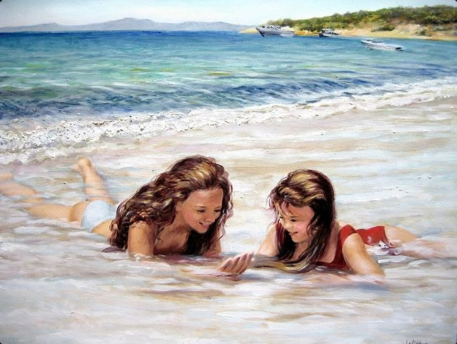 A young girl and her older companion or sister lay together in their swimsuits in brilliant blue surf on the seashore.  Gentle waves and white sand make this beach very inviting.