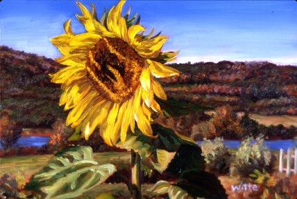 A large, yellow sunflower soaks up sunshine, with an autumn landscape in the distance.